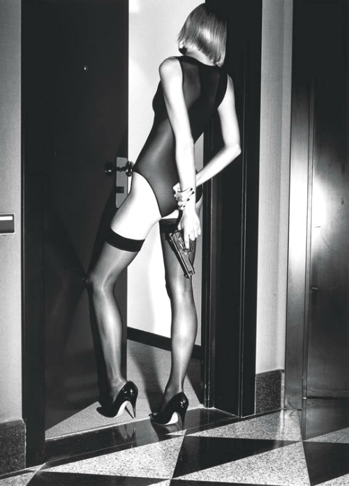 Woman with gun behind her back by Helmut Newton for Wolford Stockings, 1995Also