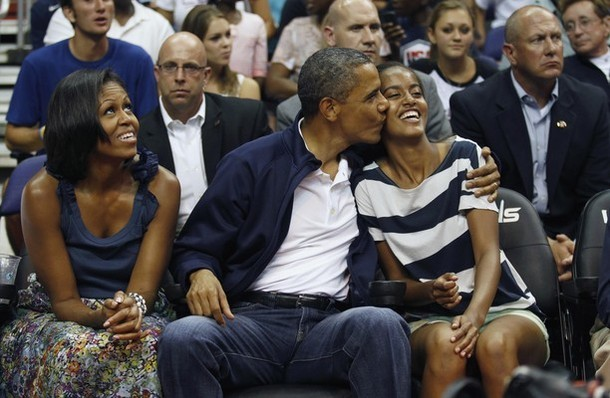 U.S. President Barack Obama kisses daughter Malia (R) as first lady Michelle Obama looks up as they attend the Olympic men's exhibition basketball game between Team USA and Brazil in Washington July 16, 2012. (via Photo from Reuters Pictures)