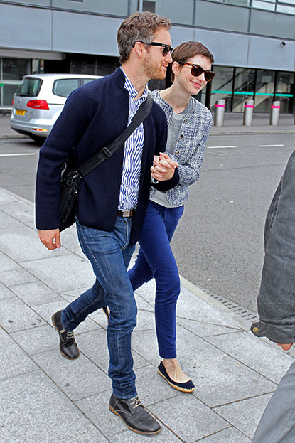 These two can't stop smiling! Anne Hathaway arriving at Heathrow Airport with her fiance, Adam Shulman to promote her new film 'The Dark Knight Rises', where she plays the part of Catwoman. Anne, who has short pixie hair for her next film role 'Les Miserables', looked very happy and held hands with Adam as they walked to their car.