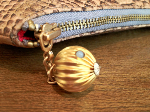 Detail of a bauble zipper-pull on a Amanda Pearl clutch.