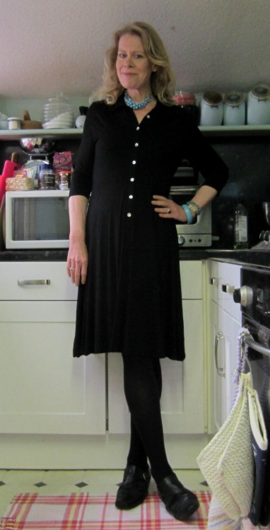Another rainy day, another closet orphan. I love shirtwaist dresses, but often find them difficult to wear confidently, as they often erase what few below-bust curves I do have. In general, I'm fairly happy with my body, and as I've written before, the only part of being tall that annoys me at all anymore is the ways in which it's inconvenient to be tall (leg room on public transport, sleeves being too short, hard to find large size shoes, etc.) but sometimes, if I'm wearing something that basically makes me look like a drinking straw with a rack, I feel uncomfortable. Enter this shirtwaist dress, which a) is made of jersey, and thus I can actually wear my regular size without dealing with gapping buttons, instead of having to go up a size and swamp the rest of my body in surplus fabric, and b) has a flared skirt that doesn't trigger my narrow-hip/nearly straight waist issues. It's kind of jacked around in the photo, but I lengthened the necklace and popped open another button before leaving the house, so it looked a lot better. For all that, though, this one may be getting tossed back into the thrift pond, because I'm really not sure I need to devote any of my limited wardrobe space to yet another plain black dress. My black Boden faux-wrap dress has a similar shape, is about the same length, and in pretty much every way could be worn on any occasion I'd wear this one. I'm going to give it some thought, but I'm very pleased to have worn it at least once to see how it worked for me. Details: Necklace: Oasis, remixed. I was looking for a necklace to break up all the funereal black on this outfit, and maybe add a little interest to what is, after all, a very plain dress, and when I spotted this one on the peg, I loved the idea of going with turquoise for my colour pop. Dress: Phase 8, thrifted. Phase 8 is such a hit-or-miss retailer for me. Some of their stuff is really very stylish and appealing, and other stuff…ugh, shuffle board on the Lido deck. No. I'm not ready to go gentle into THAT particular good night. I've always been pleased with their quality, but their sizing can be wonky. Bangles: Various, thrifted, remixed. More turquoise! Tights: Usuals, M&S. Shoes: Deichmann, remixed.