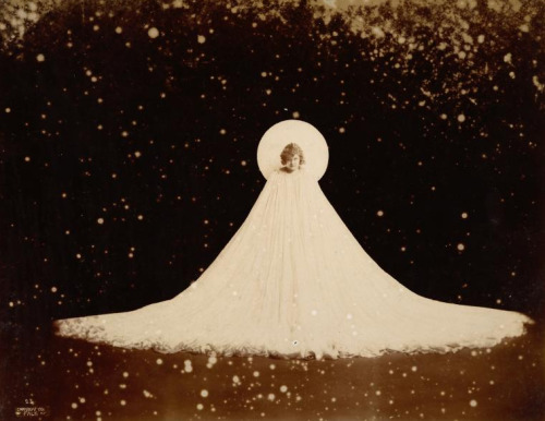 Loie Fuller in wide cape - photograph by Falk. (1901) via NYPL digital collection