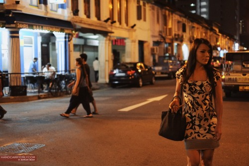 X-Pro1 Diaries: She Crosses the Road The clock read 10:52pm. The air warm and muggy, it hung like a damp blanket over everything. Beads of sweat formed on your forehead even if you were standing still, the occasional breeze offering scant relief. Late night diners hung around on the corner coffeeshops, largely keeping to themselves as they absent mindedly stared ahead, their cups of coffee producing swirls of steam into the air. Once in a while, a loud rumble of a roller shutter being pulled down announced yet another retirement for the night, as shopkeepers prepared to leave for home. A couple of stray dogs rummaged through the bins, looking for a meal as a cat across the road stared at them, seemingly unbothered. Then came a clackety clack of heels on asphalt, the stuccato rhythm out of sync with the crickets chirping in the night. A whiff of perfume mixed curiously with the night air. She crossed the road. View the rest of my ongoing X-Pro1 experiences and photos or the rest of the photos on Handcarry Only