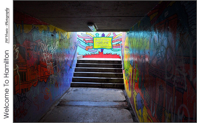 Welcome To Hamilton – (HDR/Tone-Mapped) by jwvraets on Flickr.A través de Flickr: ***For best results, click on image to view on black*** As you head North on McNab Street in downtown Hamilton, Ontario, you eventually need to cross the railway tracks serving the  downtown train station as well as being a major East-West rail traffic route. On McNab, the solution was to go under, not over, the tracks. Over time, the underpass has been decorated by local artists, although perhaps not in an official manner. Sitting near the railway station, I assume that the artistic community felt a greeting to visitors was in order and hence the title of this image. The title is taken from the text in the yellow 'box' centred above the stairs which greets all with 'Welcome To Hamilton' and then in a very helpful manner, provides a number of arrows indicating directions from that point to some of the major destinations in the core. Over time the walls of the tunnel itself have been decorated and tagged and the whole tunnel has become a bit of a surreal entrance to the downtown core. Welcome to Hamilton. - JW This image made use of an HDR-processed version of the original image although, since that involved only a single image is strictly speaking tone-mapped rather than a full HDR The image was made from a single photo captured using a hand-held Nikon D5000 fitted with a Nikkor 18-105mm VR lense set to 18mm, ISO400, Aperture priority mode, f/7.1, ISO400, 1/8 sec. HDR processing to make use of the tone-mapping stage was done using Luminance/Qtpfsgui with settings as indicated below. PP in GIMP: the tone-mapped version was loaded as the lower layer and the original image as the upper layer, the opacity of the original was set to 50% to allow some of the shadow detail of the tone-mapped layer to supplement the highlight areas of the original giving a better overall look while retaining much of the lower noise of the original, created a new layer from the result, applied tone curve tool to get better tonality, increased contrast slightly, boosted saturation overall slightly, sharpened, added fine black and white frame, added bar and text on left, scaled to 1024 wide for posting. ========================================= 1DSC_2526_mcnabunderpassgraffitiTM50pcorigadjbarsigx1024_pregamma_1_mantiuk_contrast_mapping_0.5_saturation_factor_1.4_detail_factor_1 =========================================== Qtpfsgui 1.9.3 tonemapping parameters: Operator: Mantiuk Parameters: Contrast Mapping factor: 0.5 Saturation Factor: 1.4  Detail Factor: 1  ——— PreGamma: 1