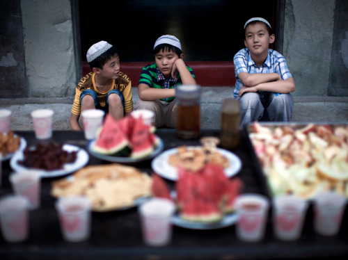 aeineh:  Chinese Hui Muslim boys waits in front of food as they wait to break their fast on the first day of the Muslim holy month of Ramadan in Beijing, August 1. (Andy Wong/Assocaited Press) #
