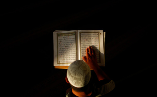 """A Palestinian Muslim man reads from the Quran, Islam's holy book, on ""fajr"" or early morning prayer, during Ramadan at a mosque in the West Bank city of Ramallah""  By: (AP Photo/Muhammed Muheisen)"