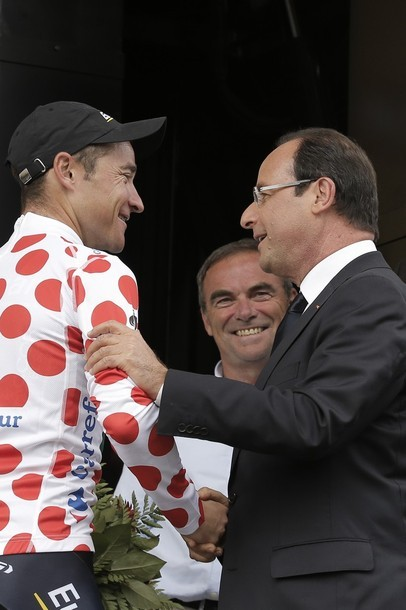 Thomas Voeckler of France, wearing the best climber's dotted jersey, is congratulated by French President Francois Hollande, right, as five-time Tour de France winner Bernard Hinault, rear, watches on the podium of the 18th stage of the Tour de France cycling race over 222.5 kilometers (138.3 miles) with start in Blagnac and finish in Brive-la-Gaillarde, France, Friday July 20, 2012. (via Photo from AP Photo)