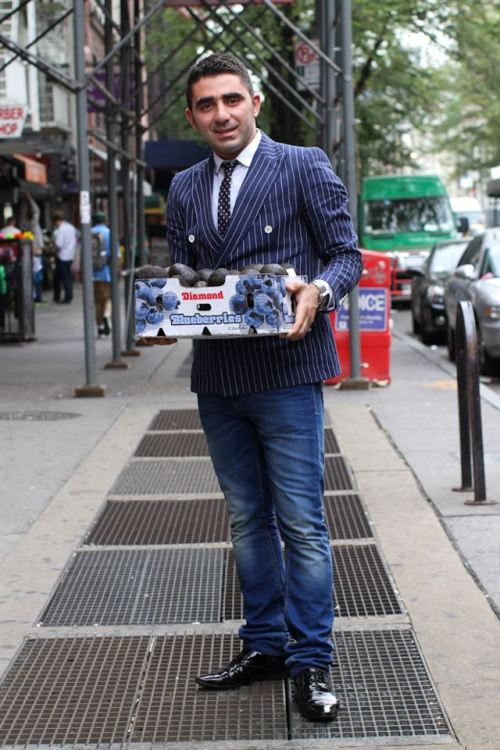 humansofnewyork:    I found this man standing near a fruit stand on the corner of 14th St and 7th Avenue. I assumed he was waiting for someone. I thought he looked awesome so I asked him for a photograph. He agreed, so I took a few quick shots and continued walking down the sidewalk. As I walked away, I scrolled through the photographs, and decided that they weren't so great. So I went back for another try. When I found the man again, he was stacking fruit. Turns out he owned the fruit stand, making him the best-dressed fruit vendor in the city.He explained that he was from Turkey, was studying International Business at Baruch College, and sold fruit to cover his expenses.