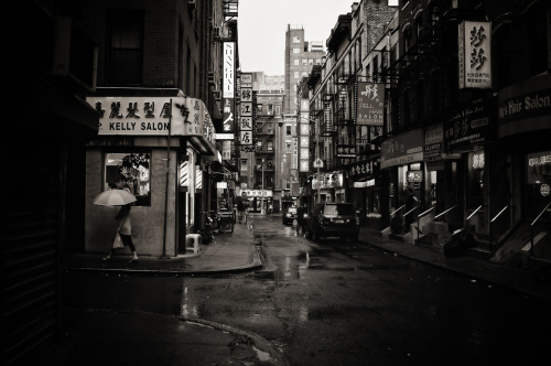 "Rain. Pell Street. Chinatown, New York City.  In-between light creates all its own stories. It's the light after a long night when the city sleepily shakes off the blanket of darkness and stretches in the first few rays of the waking sun and it's also the light after a long day when the city unwinds basking in the low light of dusk.  In-between light caught in the steady drizzle of rain is even more enchanting. Tears of laughter, heartache, sorrow and joy fall on the city streets silencing their hungry rumble. Buildings darken one by one as the city blurs softly preparing for its nightly refractory period.  —-  View this photo larger and on black on my Google Plus page  —-  Buy ""Rain on Pell Street - Chinatown - New York City"" Prints here, email me, or ask for help."