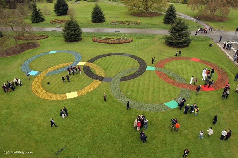Olympic officials and the media admire a large set of Olympic Rings, created with at least 20,000 flowers and plants in Kew Gardens