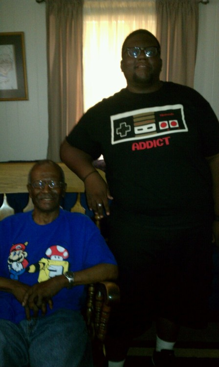 "Me and my grandfather.  Yes, he's wearing a Mario shirt.  When we found out a couple of years ago that he had early onset Alzheimer's, the doctor suggested some exercises for his mind.  He (yes, my grandfather, the same man that wouldn't let me hook my PSX up to the big screen because ""it messes the TV up and I didn't pay all this money to have you hogging my tube up"") asked about video games and the doctor said sure.  We bought him a Wii and New Super Mario Bros.  He's almost as good of a Nintendo player as me.  His mind hasn't deteriorated at all since then.  He loves playing, and asked me about getting a DS today.  I'm thinking of getting him one for Christmas.  Thanks, Mario."