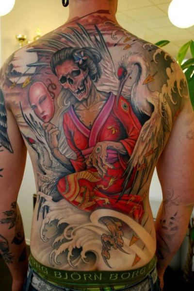 Sick Tat! Asian Angel of Death What a beautiful back piece! Asian inspired with a touch of horror and beauty all combine to make this full back piece a creative work of art. Death and beauty clash in the image as colors define the lines. This is some serious work right here! Artist piece by Johan Finne, photo by Tattoo Artist Magazine.