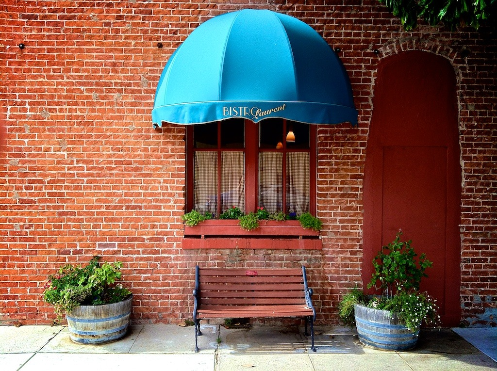 {Bistro Window} A window to the culinary delights of the Downtown Paso Robles eatery Bistro Laurent. Fine French fare in the heart Paso Robles just steps from our winery tasting room on Pine Street. The gorgeous red hue of the historic brick building sparkles on a summer day. Pictured: Bistro Laurent