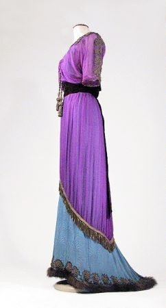 Lot 3389 Bohemian Iridescent Purple Chiffon Tea Gown French, early 20th century The calf length tunic with inverted V hem at front and point at back trimmed with metallic bronze fringe, the underdress of dusky blue jacquard with stylized chrysanthemum Deco pattern, small train at back trimmed in fur and metallic bronze passementerie lotus leaves, the same trimming the V-necked bodice and along shoulder down short kimono sleeves with briar stitching, two braids with faux tassels down center front, bronze lace trimmed inset with gold print on creme chiffon overlay, crushed wide chocolate velvet ribbon sash tied at back in bow with long streamers, size 2/4, labeled: Lichenstein Cie Modes/Paris/New York. UnsoldEstimate $1,500-1,800