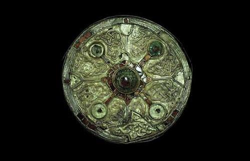"Harford Farm Disc Brooch, ~7th century. ""This Anglo-Saxon brooch dates from about 610-650AD. It was found in a grave at Harford Farm in Norfolk…. Inscribed either side of the pin mounting are two snake-like creatures, head to tail, biting each other's feet…."" Source: www.museums.norfolk.gov.uk"