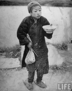 Starving child holding out an empty rice bowl during famine Photographer: George Silk China, 1946. © Time Inc.