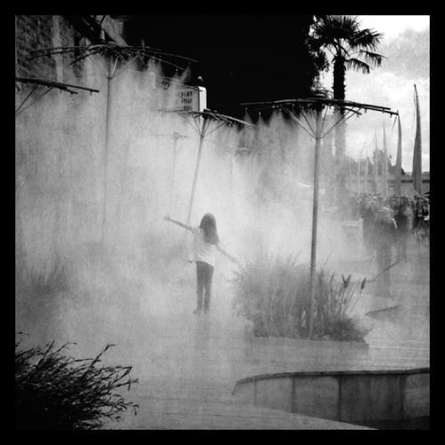 newsweek-paris-france:  Girl in the artificial mist at Paris Plage this afternoon. Paris, France. For more in this series see Rues de Paradis.