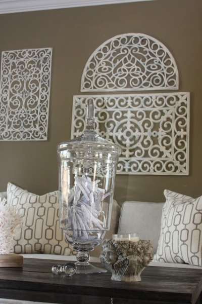 "a living room fit for a modern-day House Greyjoy: ""iron-wrought"" wall decor, wooden tables, and nautical and cement accents DIY ""iron-wrought"" wall decor: Rubber Door Mat, spray paint"