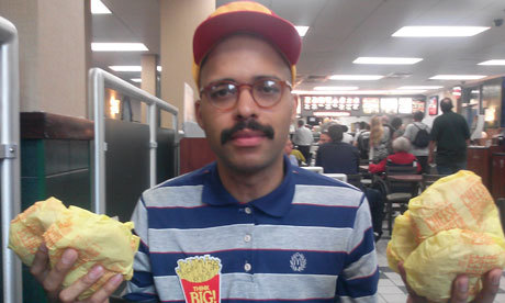 Performance artist Nate Hill is throwing McDonald's burgers to (at?) people two nights weekly this summer.