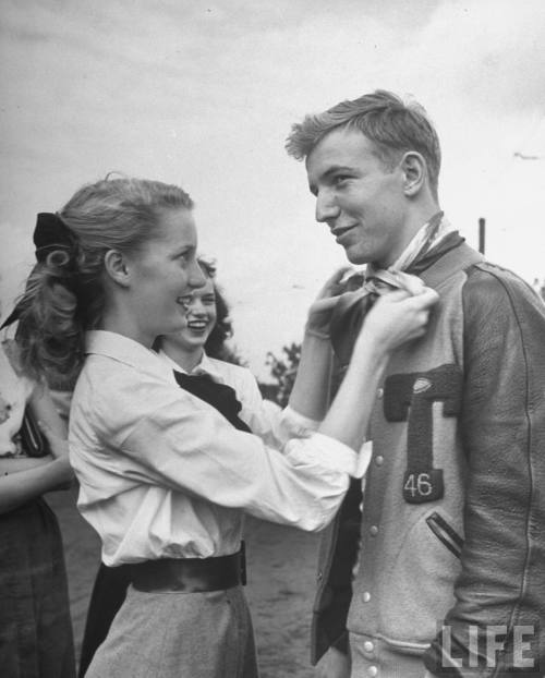 bygoneamericana:  Teenage girl tying a scarf around the neck of her boyfriend as a fad. Atlanta, 1947. By Ed Clark