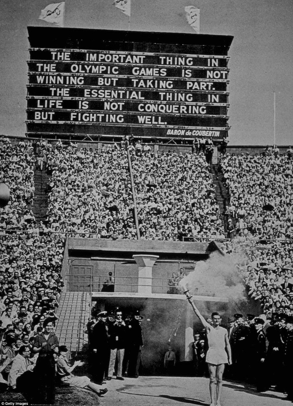 plane-ticket:  The last time the Summer Olympics were held in London was in 1948. Here's a picture of the Olympic torch being presented at the Games at Wembley Stadium.