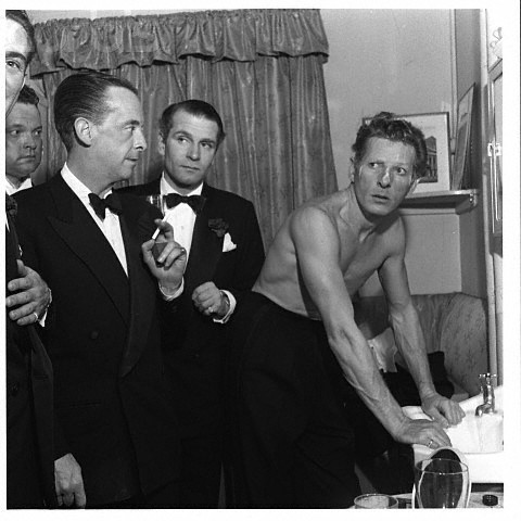 Danny Kaye is caught in the middle of washing off his make-up in a dressing room shared with (from left to right) Orson Welles, Robert Helpman and Sir Laurence Olivier. 1951