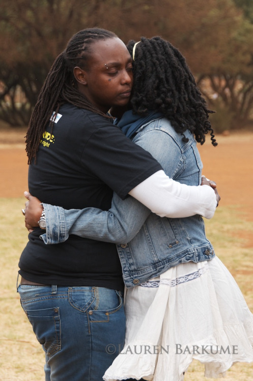 [Image: Photo of two dark-skinned women embracing. One has on a t-shirt and jeans, the other a jean jacket and white skirt. They are outside.] Soweto Pride Sept 2011 125 (by Lauren Barkume)
