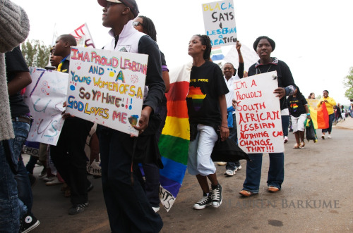 "[Image: Photo of a procession of people at a pride event, many holding signs and rainbow flags. One sign reads, ""I'm a proud lesbian and a young women of S.A. so Y? hate!!! God loves me,"" and another, ""I'm a proudly South African Lesbian nothing can change that!!!""] Soweto Pride Sept 2011 86 (by Lauren Barkume)"