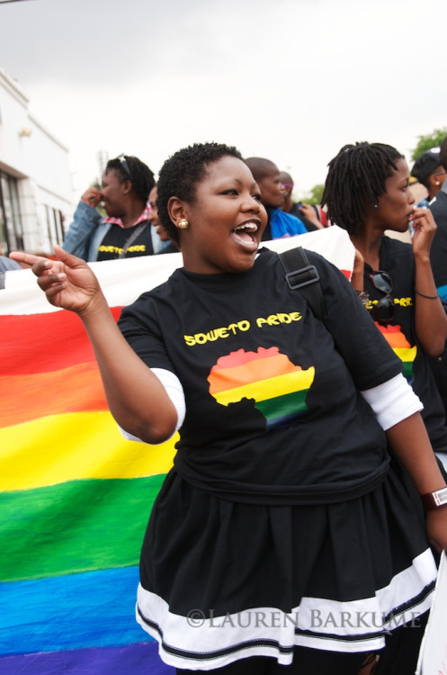 [Image: Photo from a pride event of a grinning, dark-skinned woman in a rainbow Africa/Soweto Pride t-shirt and a skirt, expressive with one hand in the air, in front of a rainbow flag.] Soweto Pride Sept 2011 19 (by Lauren Barkume)