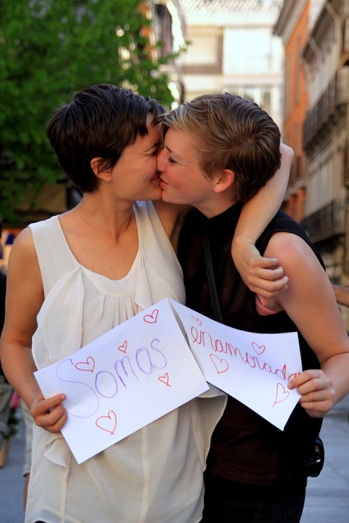"[Image: Photo of two short-haired, light and tan-skinned women kissing while grinning/laughing. They are embraced side to side and are each holding up a piece of paper; one's reads, ""Somas,"" and the other's, ""enamorada""] Día de la Visibilidad Lésbica (by BiancaJAnderson)"
