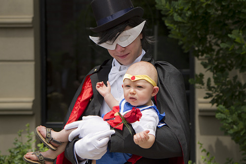 cosplayingchildren:  A parent dressed as Tuxedo Mask cradles a baby Sailor Moon.