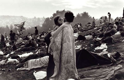 "Woodstock Memories  Forty Three years ago, an event that defined a generation took place in Bethel, NY. For a few days, music, peace and love reigned supreme. Of all the images snapped during the original Woodstock weekend, one stands above all: a young couple huddled together in a blanket, standing alone in a sea of people lying on wet ground. It's an enduring image of love, care and protection that earned iconic status through its placement on the cover of the original ""Woodstock"" album in 1970, as well as on the movie poster. Forty years later, the couple in the photo — Nick and Bobbi Ercoline, both 60 — remain together. They married two summers after the fabled weekend, and they still live less than an hour's drive from the original concert site of Bethel, N.Y., and within spitting distance of where they both grew up. Nick Ercoline works for the Orange County, N.Y., Department of Housing. Bobbi is a resident nurse at the elementary school in their hometown of Pine Bush. The 40th anniversary of the ultimate hippie be-in, this Aug. 15-17, has thrown the Ercolines into the spotlight again — something they never expected or sought. They say they remember nothing of the original shot, taken by Burk Uzzle. ""We weren't striking a pose,"" Nick says. ""We were as surprised as everybody to see that photo on the album cover."" They discovered it while at a friend's house listening to the album and passing around the gatefold jacket. First, Nick recognized the famous yellow butterfly staff in the left corner. ""It belonged to this guy Herbie,"" Nick says. ""We latched on to him that day because he was having a very bad experience. He was tripping pretty heavily and he had lost his friends. After I saw that staff I said, 'Hey that's our blanket.' Then I said, 'Hey, that's us.'"" Bobbi, then 20, wasn't overly impressed. ""Woodstock was over and done with at that time,"" she says. ""It didn't seem like a big deal. The only thing was that then I had to tell my mother I had gone. She didn't know. But by then, she didn't mind."" The two had arrived in the middle of the weekend, a rare feat given that all main roads were closed by then. ""We were local kids, so we knew the back roads,"" Nick says. ""About 5 miles away we abandoned this big white 1965 Chevrolet Impala station wagon."" The two didn't realize the impact their photo had until Woodstock's 20th anniversary, when the world's media began seeking them out. In fact, their memories of the original event have more to do with the scene than the music, because they were too far away to hear or see much. ""I remember the rain, the lack of toilets and the body odor,"" Bobbi says. ""I also remember an orange haze from the glowing lights of the stage. It was everywhere, lighting up the sky."" The pair had met only three months earlier, over Memorial Day weekend, at the bar where Nick worked. ""This waiter brought this beautiful blond in one day and said, 'This is my girlfriend; keep an eye on her,'"" Nick explains. ""Every night she stood in front of me and we got friendlier and friendlier. Then one weekend he made the mistake of leaving her home while he went to the shore with the guys and he never told her. That was the end of that. And the beginning of this."" Despite all the time gone by, Nick says they still get recognized. ""We were in Germany, and right when we walked into the hotel they knew who we were."" As to why their photo was chosen, Nick has a theory. ""It's peaceful, which is what the event was about,"" he says. ""And it's an honest representation of a generation. When we look at that photo I don't see Bobbi and me. I see our generation."" Festivals end, music quiets down, body odors evaporate, but love — true love — endures."