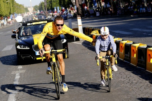 fuckyeahcycling:  Overall leader's yellow jersey, British Bradley Wiggins, parades with his son at the end of the 120 km and last stage of the 2012 Tour de France cycling race starting in Rambouillet and finishing in the famous Paris-Champs-Elysees Avenue, on July 22, 2012. (via Photo from Getty Images)