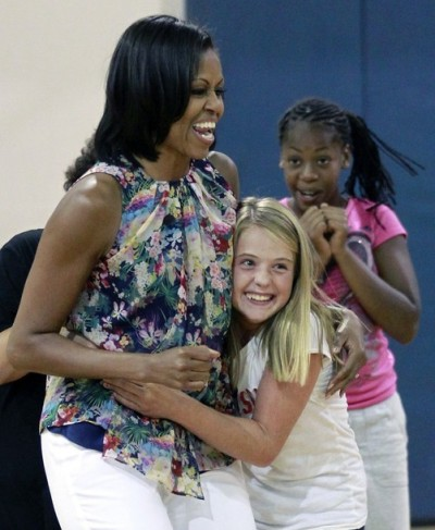 Michelle Obama getting super hugged by a girl.