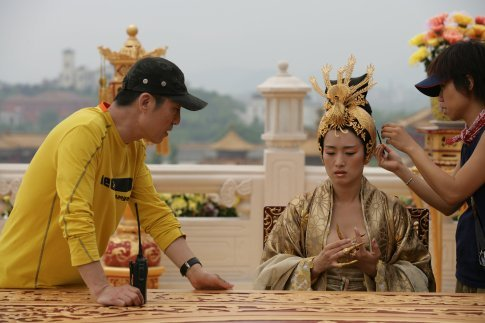 "Director Zhang Yimou with actor Gong Li on the set of the 2006 film ""Curse Of The Golden Flower"". Click the pic to watch a scene from the movie."
