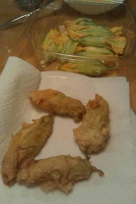 videorose:  Ricotta-stuffed Fried Squash Blossoms serves 4-6 you'll need 1 box of squash blossoms (about 20) from your local farmer's market -  mine are from NY's Evolutionary  Organics inspect the blossoms for cleanliness & freshness, gently pick out the stamens inside the flowers. chop about 2 tablespoons of fresh herbs (basil & sage is what we used) mash together the herbs, salt & pepper, and about 1 cup of fresh ricotta. for special food like this, use a really good ricotta like Narragansett Creamery's. gently stuff each blossom with the ricotta mixture. i didn't find a spoon at all useful, fingers were much easier. beat two eggs in a separate shallow bowl. make a dredge of flour, salt & pepper. heat ample oil in a sauce pan or heavy skillet until it's hot enough for deep frying. when the oil is hot, dip each stuffed flower in the egg and then the flower, and gently drop them into the hot oil. fry only a few at a time. fry the blossoms 3-4 minutes until they are golden. dip them out with tons & let drip onto a plate covered with paper towels. let cool slightly, then devour.