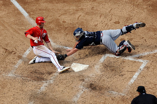 Brian McCann tags Bryce Harper out at home plate during the sixth inning of Sunday's Nationals-Braves game at Nationals Park. Despite this missed run, Washington prevailed 9-2. (Photo by Patrick McDermott/Getty Images) SHEEHAN: How six teams should navigate a tricky trade market