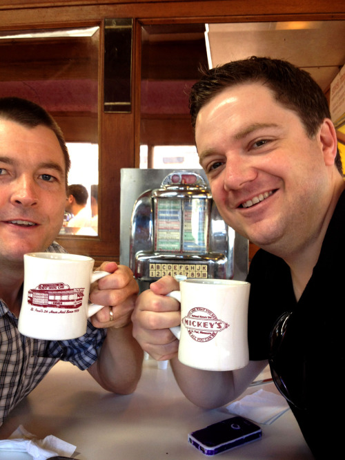 "Mugshot Monday - ""Mickey's Dining Car"" coffee mug with special guest appearance by Christopher Pollard Mickey's Dining Car in St. Paul is a great place for breakfast regardless of the time of day. They're even open 24 hours a day, 365 days a year. If you've never been there, it looks like an old-school railroad dining car — and it's super cozy. Mary, our waitress, was full of sass and (rightfully) gave me grief for wanting a Mickey's branded coffee mug instead of the plain white one I was originally served. Chris got one with a logo, after all. ""We don't have many of them. He got the last one. Dontchya know you can buy your own? Geez."" So I bought one. Mary eventually asked about Mugshot Monday and I showed her the gallery of photos on my phone. ""I hate these phones,"" she said. But she mentioned she owns about 200 coffee mugs! She said her favorite coffee mug, the one that was her dad's and that reminded her of her dad, was stolen from the diner one day. That's just terrible. Mary asked about our kids, told us about her grand-kids, and mentioned her dad was a sign painter back in the old days. ""They don't need sign painters no more these days. It's all done by computers. But the signs, they don't look good."" It was fun meeting Chris (and Mary) for breakfast today. Actually, Chris' Mugshot Monday shot turned out WAY better than mine did:"