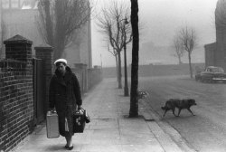 Journalist Katharine Whitehorn carries her luggage along a foggy London street Photographer: Bert Hardy (Picture Post/Getty Images) London, England, 1956. Original Publication: Picture Post - Big City Loneliness