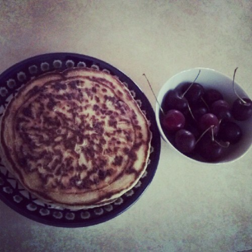 Chocolate chip pancakes with nothing on them and cherries.