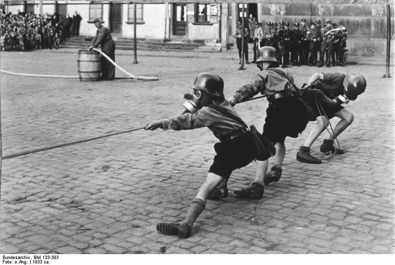 "pzychokittie:  ""Hitler Youth members playing tug of war while donning helmets and gas masks, 1933"" It's kinda cute."