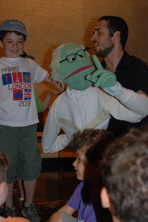 "A young audience member tells stories with Jacob and a wise puppet at Summer Sundays. Family Program News: Jacob Stein and The Bakery Band Puppets Make their Summer Sundays at the Center Debut  ""We appreciated that things were very casual and welcoming at the Center. Our kids very much enjoyed the performance. We are so happy to know about the family programs and will definitely attend again."" – Parent, Manhattan Last Sunday, families escaped the city heat and gathered in the Center's Great Hall for the second Summer Sundays at the Center program, which featured a music-filled performance by Jacob Stein and The Bakery Band Puppets. Jacob's comical cast of characters—that ranged from a stubborn rooster to a dancing goat—had the whole crowd dancing and singing along to a wonderful show about the wise folk of Chelm, Poland, complete with new material as well as beloved tales and traditional songs. It was a delight to see generations of family members come together for the event, and we are looking forward to more fun at Jacob's next performance at the Center on August 12th!"