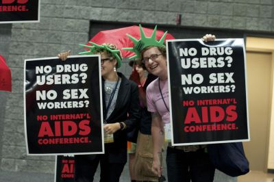"Sex workers and their allies staged a protest during press conference held on the opening day of the International AIDS Conference. More than 20 protesters rushed to the stage during the press conference chanting, ""No drug users, no sex workers, no I… A… C…"" Many sex workers and drug users have been unable to enter the United States due to immigration restrictions on anyone who may have used drugs or engaged in sex work. After the action protestors carried their signs to other parts of the building to inform arriving participants of the lack of representation at the 2012 International AIDS Conference."