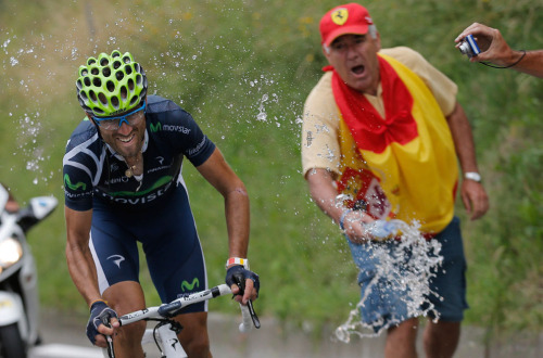 A spectator wrapped in the Spanish flag sprays water on stage winner Alejandro Valverde of Spain as he climbs towards Peyragudes during the 17th stage of the Tour de France, on July 19, 2012. (AP Photo/Christophe Ena) (via The 2012 Tour de France, Part 2 of 2 - In Focus - The Atlantic)