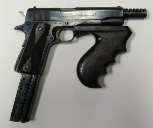whiskey1-7:  The rare prototype for the Colt 1911 PDW. Basically a fully automatic M1911 with an extended magazine and foregrip.   This isn't a prototype, these were home-modified guns that were put together by gangsters using a Thompson foregrip and an extended magazine. Notable,  John Dillinger's gang had a few of them.   and here is a someone's modern interpretation:  It's illegal to put a foregrip on a pistol though.