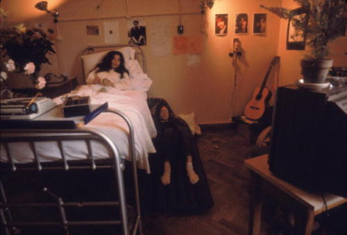 thebeatlesordie:  thegilly:  John stays by Yoko's side after her miscarriage in 1968. Photos by Susan Wood.  ♥ I also love how there's pictures of Ringo, George, and Paul on the wall
