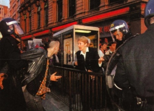 beginningthebeguine:  youaintpunk:  The riots also offered a glimpse into how photographs can be used out of context: 'Sir: In last week's article about the poll-tax riot in Trafalgar Square ('THE MOB'S BRIEF RULE', 7 April) there is a large photograph labelled 'A West End shopper argues with a protester'. The woman in the photograph is me, and I thought you might like to know the true story behind the picture. I was on my way to the theatre, with my husband. As we walked down Regent Street at about 6.30pm, the windows were intact and there was a large, cheerful, noisy group of poll-tax protesters walking up from Piccadilly Circus. We saw ordinary uniformed police walking alongside, on the pavement, keeping a low profile. The atmosphere was changed dramatically in moments when a fast-walking, threatening group of riot-squad police appeared. We walked on to the top of Haymarket, where the atmosphere was more tense and more protesters were streaming up Haymarket from the Trafalgar Square end. Suddenly a group of mounted police charged at full gallop into the rear of the group of protesters, scattering them, passers-by and us and creating panic. People screamed and some fell. Next to me and my husband another group of riot-squad appeared, in a most intimidating manner. The next thing that happened is what horrified me most. Four of the riot-squad police grabbed a young girl of 18 or 19 for no reason and forced her in a brutal manner on to the crowd-control railings, with her throat across the top of the railings. Her young male companion was frantically trying to reach her and was being held back by one riot-squad policeman. In your photograph I was urging the boy to calm down or he might be arrested; he was telling me that the person being held down across the railings was his girlfriend. My husband remonstrated with the riot-squad policeman holding the boy, and I shouted at the four riot-squad men to let the girl go as they were obviously hurting her. To my surprise, they did let her go – it was almost as if they did not know what they were doing. The riot-squad policemen involved in this incident were not wearing any form of identification. Their epaulettes were unbuttoned and flapping loose; I lifted them on two men and neither had any numbers on. There was a sergeant with them, who was numbered and my husband asked why his men wore no identifying numbers. The sergeant replied that it did not matter as he knew who the men were. We are a middle-aged suburban couple who now feel more intimidated by the Metropolitan police than by a mob. If we feel so angry, how on earth did the young hot-heads at the rally feel?' Mrs R.A. Sare, Northwood, Middlessex Source  BOOM.