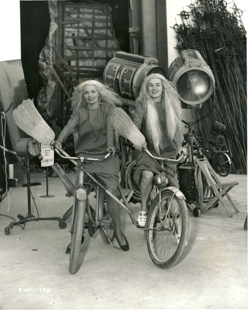 Thais Wilson and Mary Brewer ride bikes. And brooms. And wigs.
