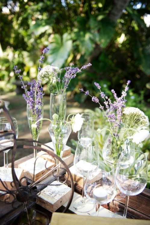 Flowers in champagne and wine glasses // photo by Ashley Camper