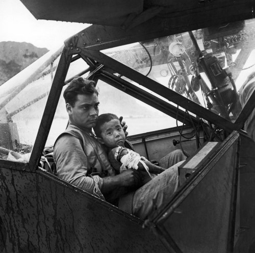 collective-history:  An American pilot holds a wounded Japanese boy during the WW2 Pacific battle on the island of Saipan as they await to fly to the nearest field hospital, 1944.